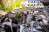 istock Cars mechanic is checking the level of engine oil. 1280863974
