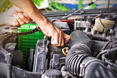 istock Cars mechanic is closing the engine oil lid after adding the oil to the engine to the level. 1264619040