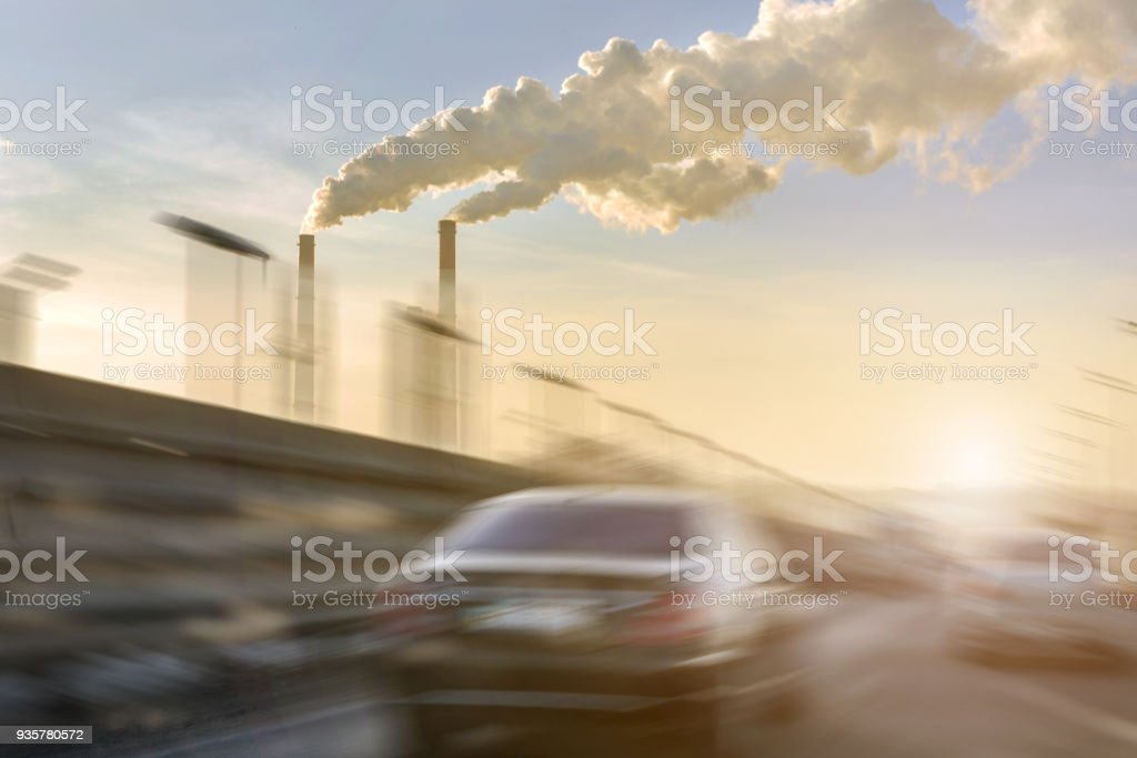 Cars moving fast on city highway. Smoking factory pipes with white clouds of smog on background. Motion blur. Sunset light. Industrial urban cityscape concept stock photo
