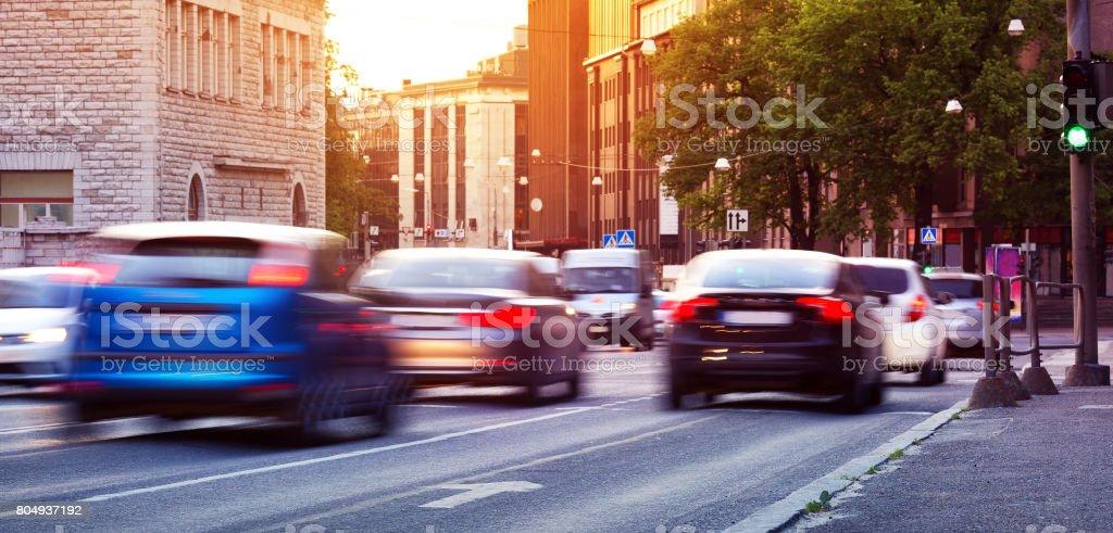 Coches que se mueven en el camino urbano al atardecer - foto de stock