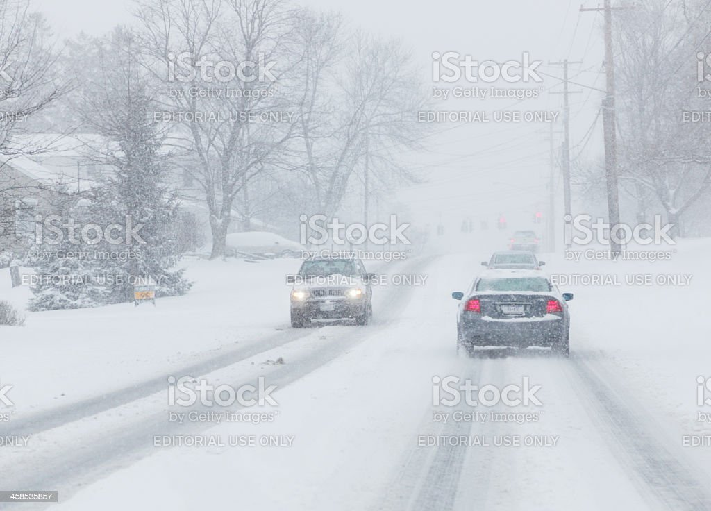Cars on Road Moving Slowly in Winter Snow Blizzard royalty-free stock photo