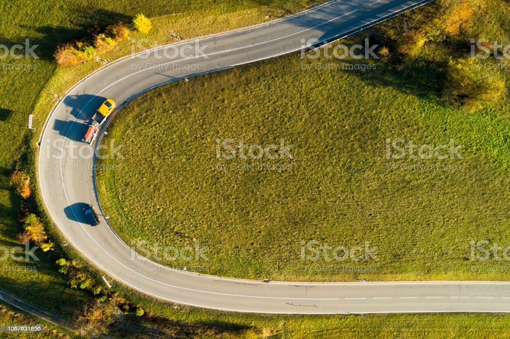 Cars on the bend of the road in autumn, aerial view.