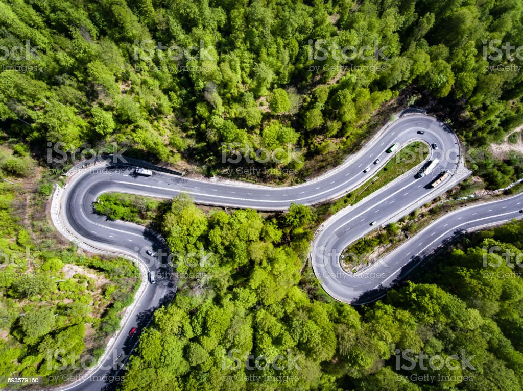 Cars on winding road trough the forest, Transfagarasan, Romania stock photo