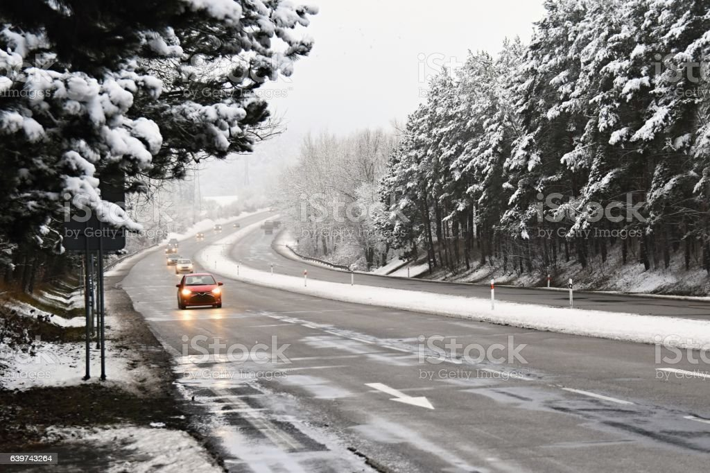 Cars on winter road with snow.Dangerous traffic in bad weather stock photo