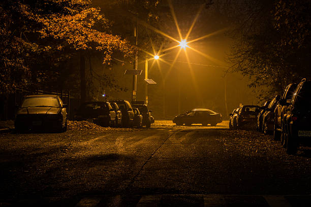 cars parked at night - mist donker auto stockfoto's en -beelden