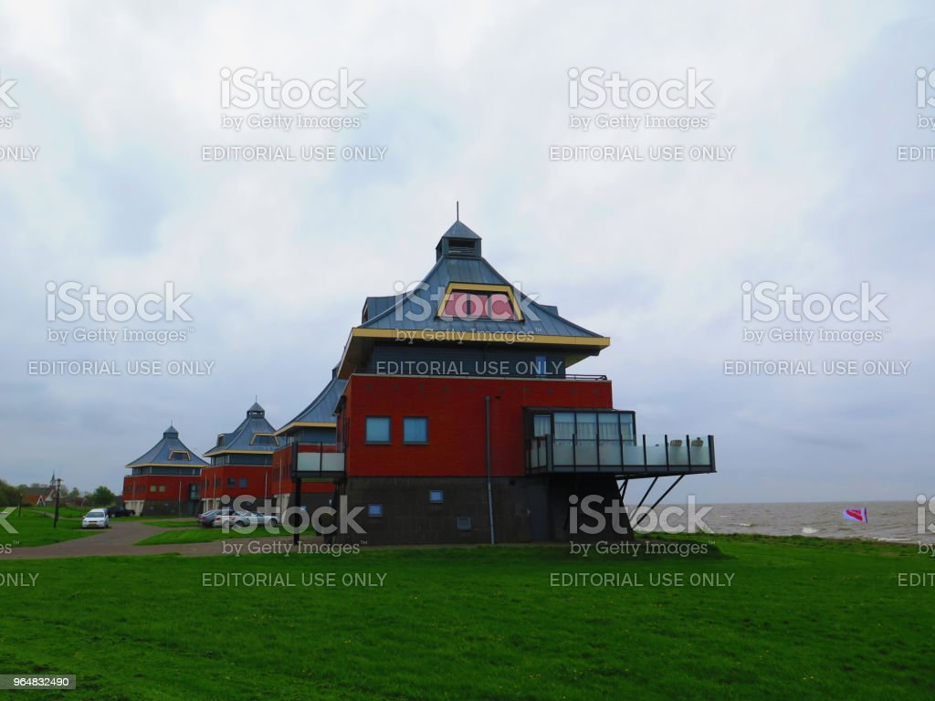 Cars parked by Colorful large buildings in Dutch fishing village royalty-free stock photo