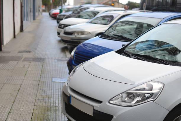 coches estacionados en una fila en una calle de la ciudad - inmóvil fotografías e imágenes de stock
