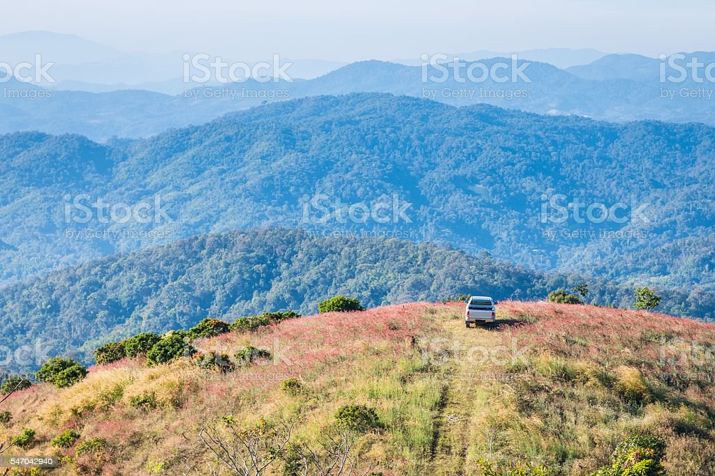 Cars parked on a hill overlooking a beautiful mountain stock photo