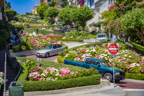 cars passing the Lombard street in San Francisco. It is  known for the  section on Russian Hill between Hyde and Leavenworth, in which the roadway has eight turns stock photo