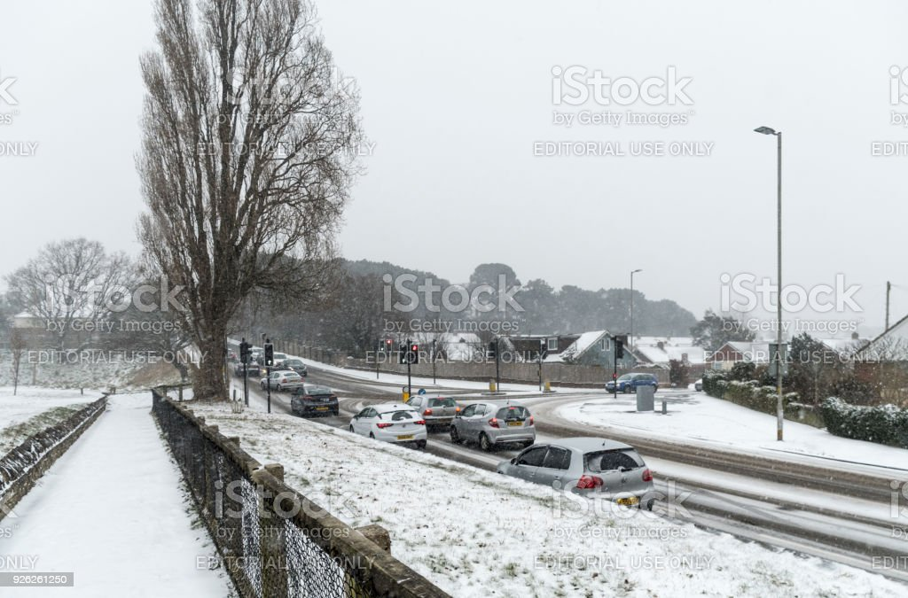 Cars queuing at Junction of Alder Rd and Weymouth Rd in Poole in the snow stock photo