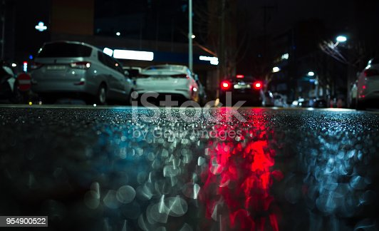 istock Cars red stop lights reflection on wet asphalt 954900522