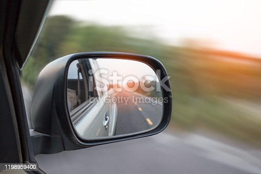 Cars run through the street from the Gray car's side view mirror. Road Car Rear View Mirror Motion Blur Background (Vintage Style)