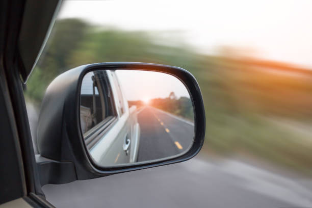 Cars run through the street from the Gray car's side view mirror. stock photo
