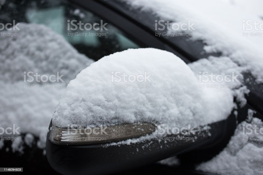 Car\'s side view mirror of a modern car covered with snow