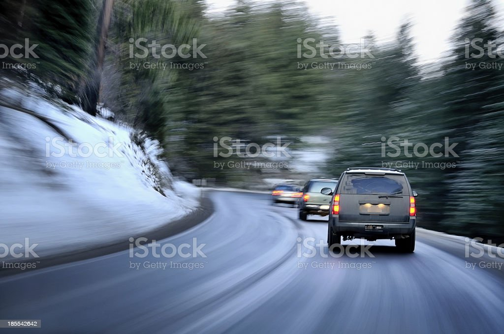 Cars speeding along a wet winding winter road stock photo