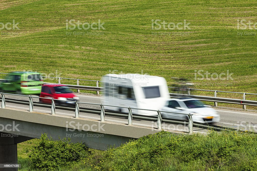 Cars Speeding on Elevated Highway Over Green Hills royalty-free stock photo