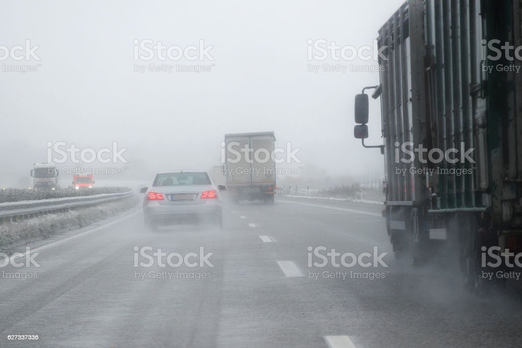 cars, trucks and rescue vehicle driving in dangerous winter weather stock photo