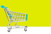 Cart from the grocery store on a yellow background. Retail trade and advertising. Purchase in the store.