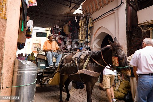 Marrakesh, Morocco - September 25, 2008: a man on cart pulled by a donkey in an alley of the medina of Marrakesh in Morocco.