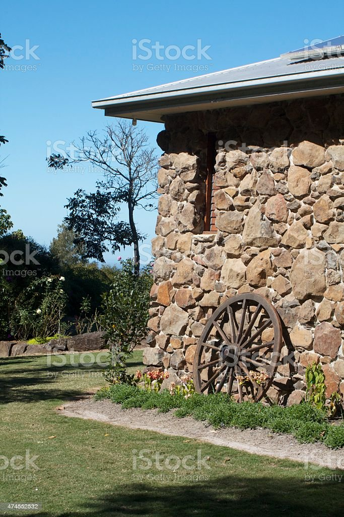 Cart Wheel Leaning Against a Stone House stock photo