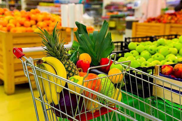 cart with fresh fruits and vegetables in shopping centre - kürbis kaufen stock-fotos und bilder