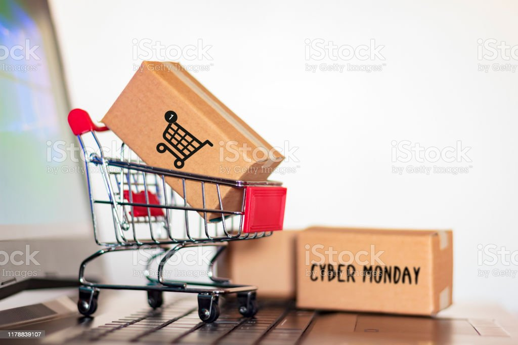 Carton box and and trolley on laptop computer. Online shopping and Cyber Monday shopping concept - Стоковые фото Бизнес роялти-фри