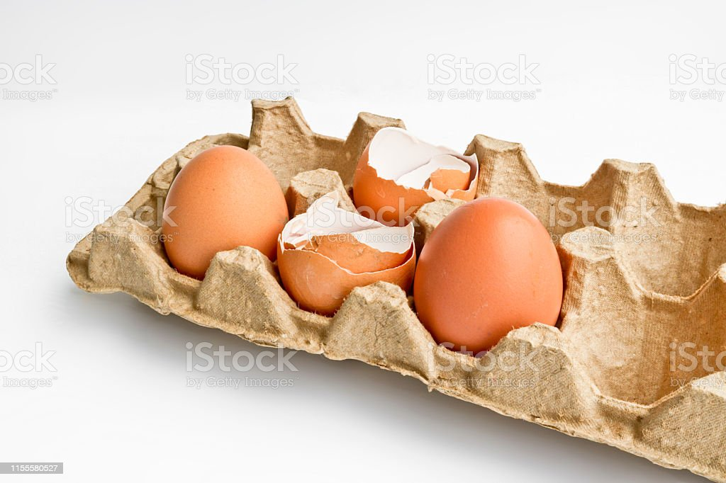 Carton packaging for eggs with broken eggshell and eggs on a light...