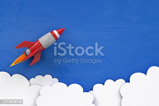 Fun retro 3d cartoon rocket or space shuttle on painted blue background with copy space with clouds after take off.