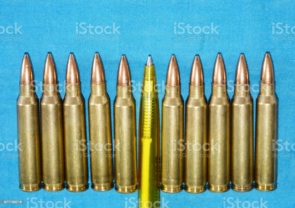 Cartridge 5 56 Mm Caliber With Pen as a Concept of Propaganda in Mass Media. Fake News Invasion Concept. stock photo