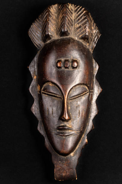 Carved African Mask Souvenir African mask souvenir isolated on a black background. Gift concept. carving craft activity stock pictures, royalty-free photos & images