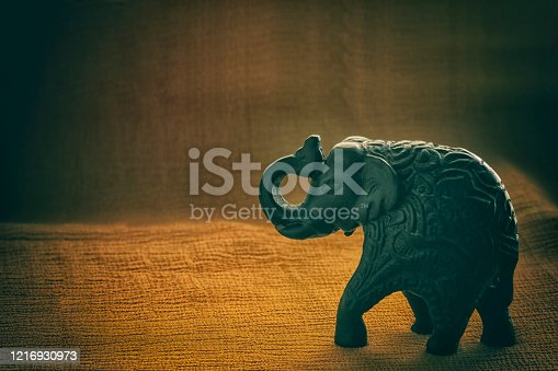 Carved elephant on yellow textured cloth with back light