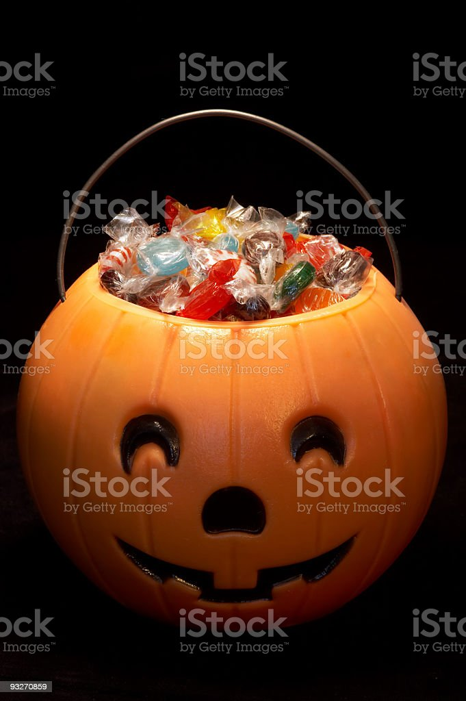 A carved Hallowe'en pumpkin filled with candies stock photo