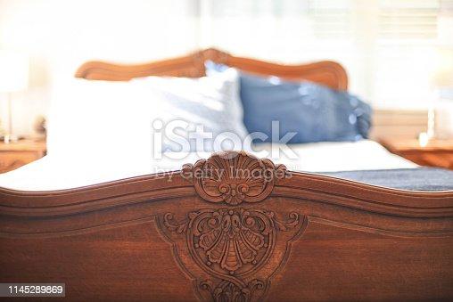 Closeup of wood carving craftsmanship on antique oak footboard