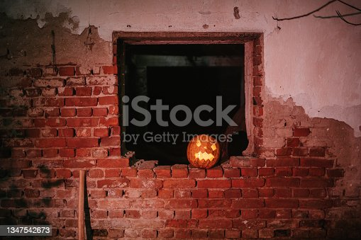 istock Carved pumpkin on a window 1347542673