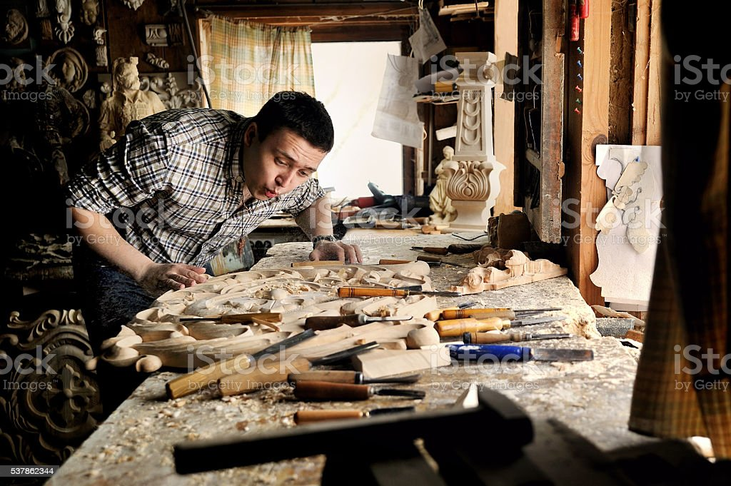 Carver in workshop of wood carving blow off sawdust stock photo