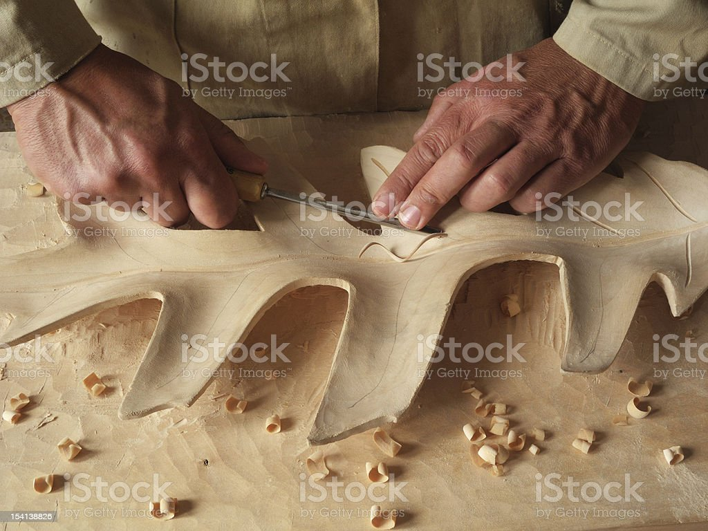 carving a leaf in wood stock photo