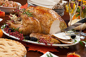 Carving roasted pepper turkey for Thanksgiving, garnished with pink pepper, blackberry, and fresh rosemary twigs on a dinner table decorated with mini pumpkins, beans, carrots, baked potato, pie, cranberry relish, gravy, flowers, candles, and flutes of champagne.'n