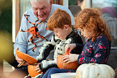 Two children and their grandfather are decorating pumpkins together on the porch step.
