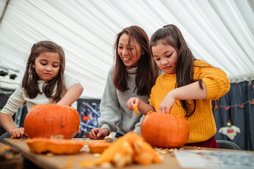 Mother and daughters carving pumpkins at a farm after picking them at a farm in preparation for Halloween.