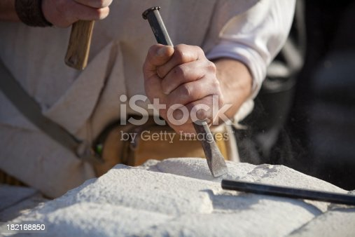Carving stone in the sun with hammer and chisel