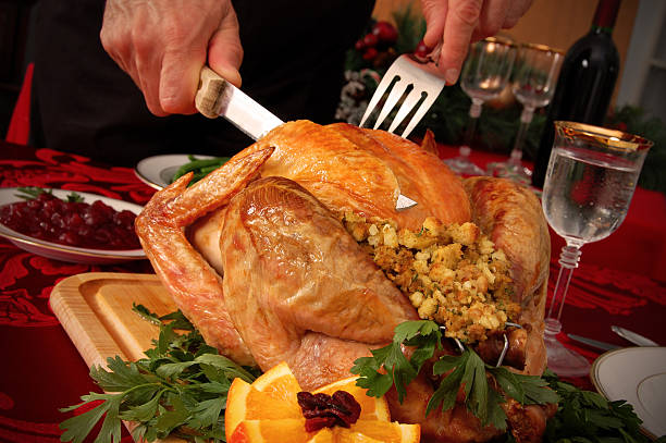 Carving the Christmas Turkey A man beginning to carve a turkey for Christmas dinner at a festively decorated table. carving knife stock pictures, royalty-free photos & images