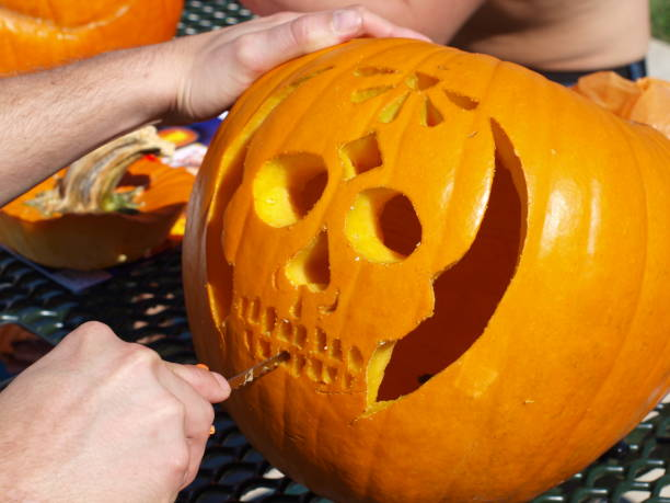 Carving the Teeth of a Pumpkin for Decorations stock photo