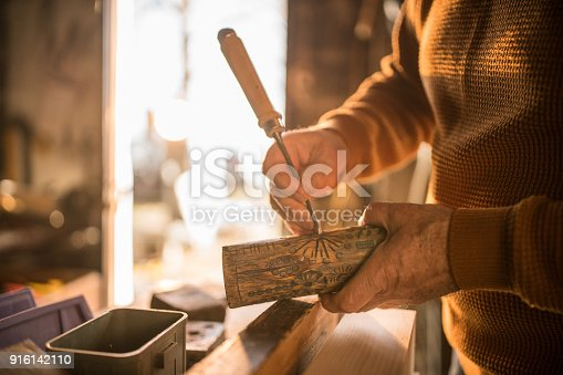 Senior man carving wood and making art in his carpentry work shop