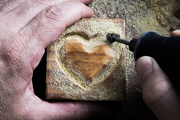 carving wood heart - dremel wood stock photos and pictures