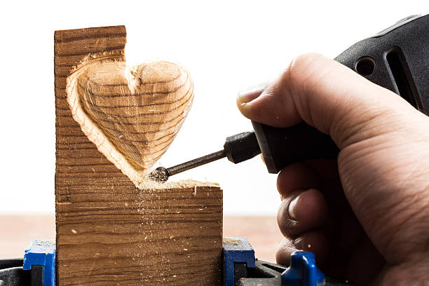 carving wood heart, white - dremel wood stock photos and pictures