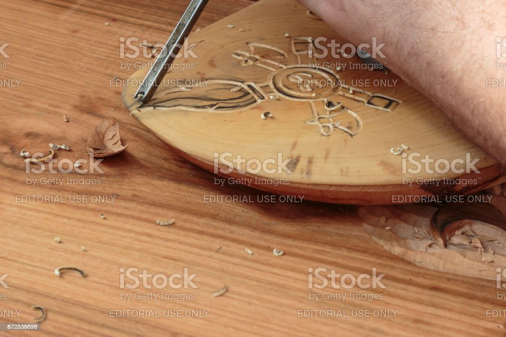 Carving Wood with Engraver Tool stock photo
