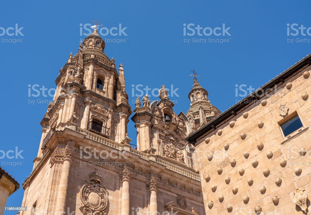 Casa de la Conchas and Le Clericia church in Salamanca Spain Ornate stone carvings on the Casa de la Conchas or shells and the Clericia church or cathedral in Salamanca Architecture Stock Photo
