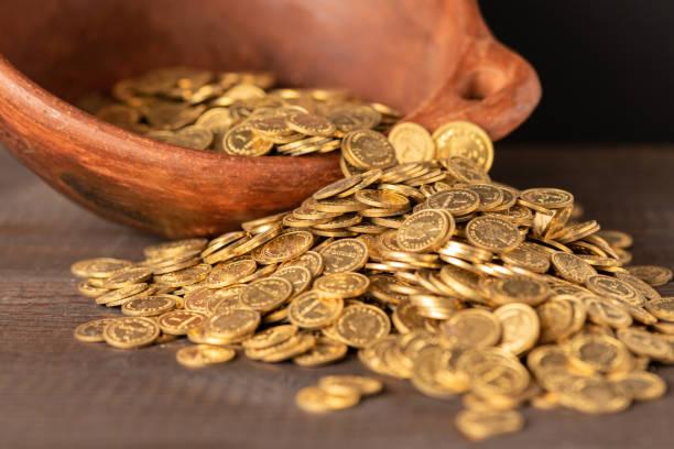 Kaskade von kleinen goldenen Münzen aus einem Topf – Foto