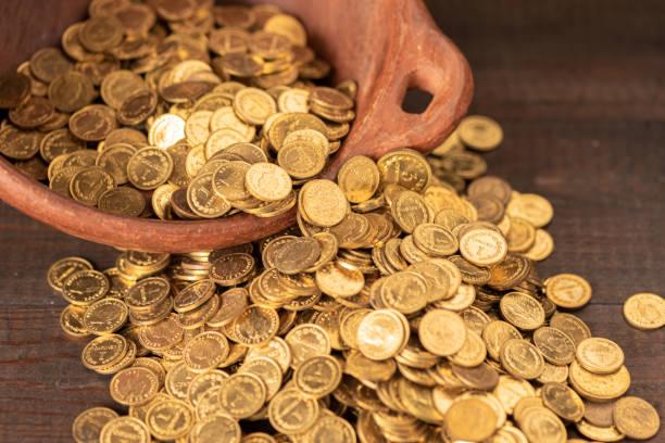 Kaskade von kleinen goldenen Münzen aus einem Terrakotta-Topf – Foto