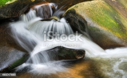 Detail of small beautiful cascade between mossy stones.